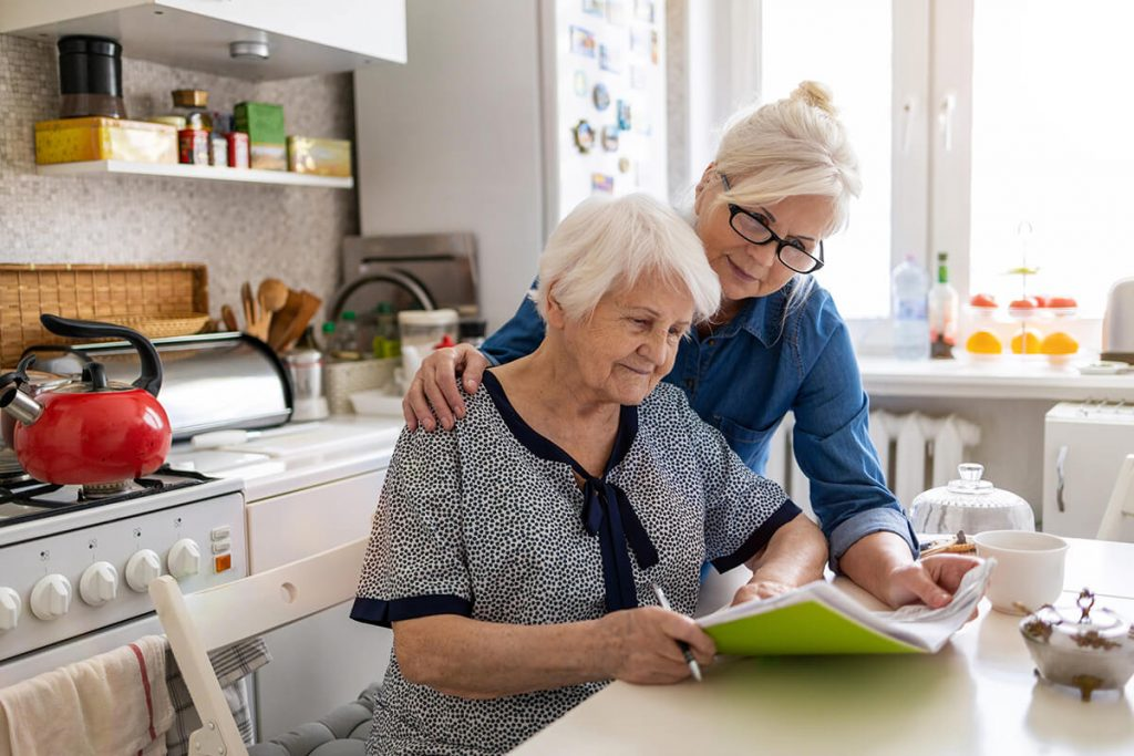 Mature woman helping elderly mother